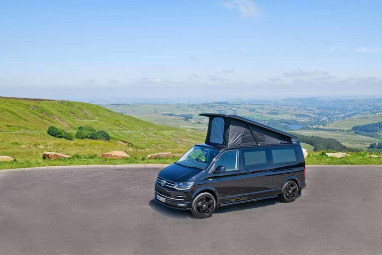 VW camper van overlooking a valley with overhead sleeping space extended up