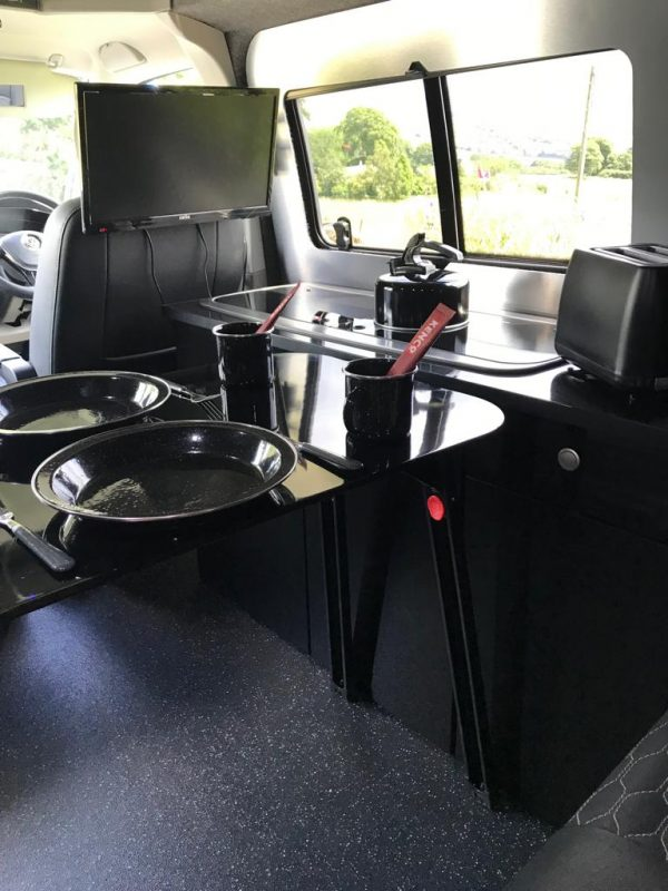 VW camper van table setup with kettle on the cooker