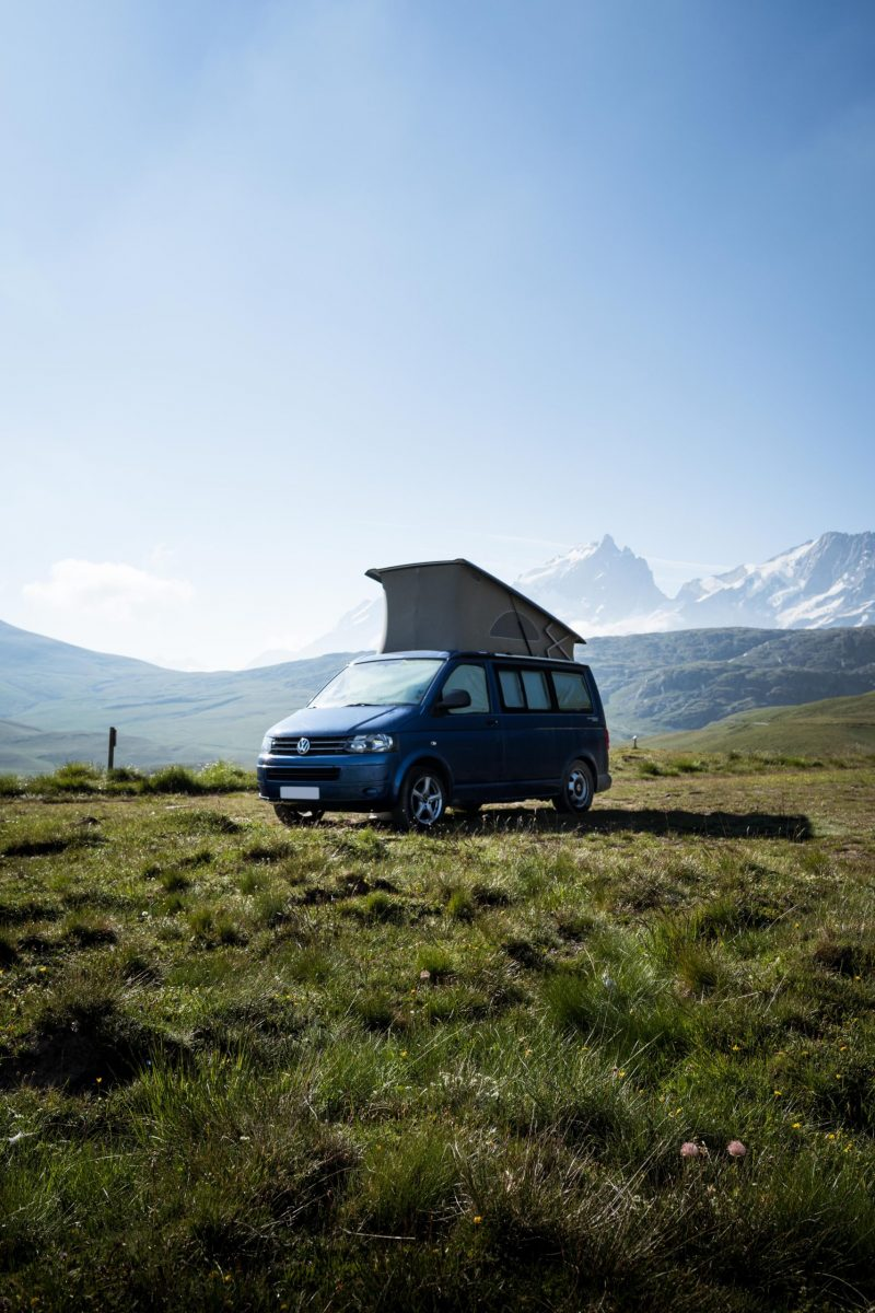 VW camper van in a field with mountains in the background