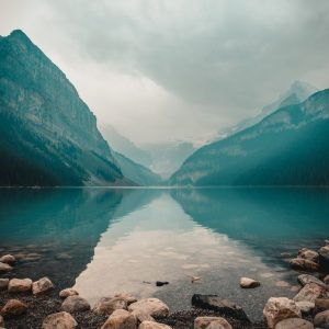 Low angle shot of lake surrounded by cloudy mountains