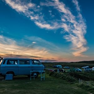 Old VW camper van in a field at sunset