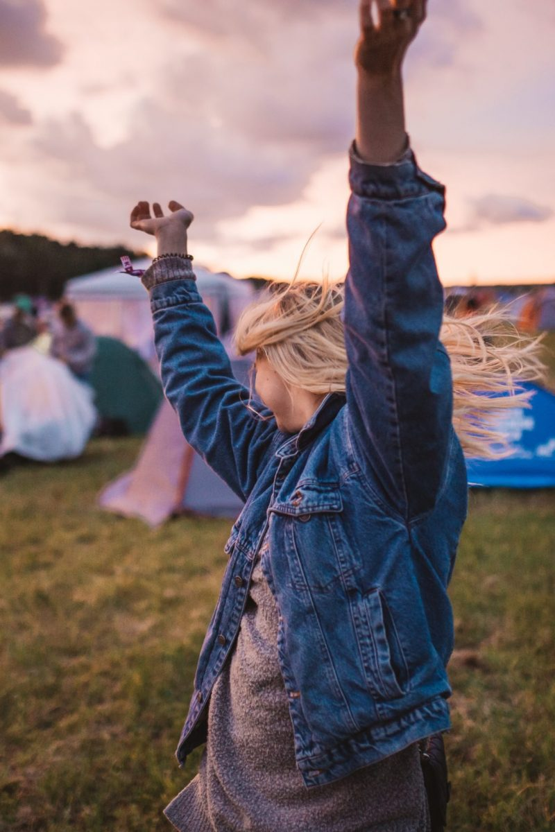 Woman dancing at a festival with tents in the background